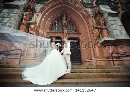 Wedding couple near a church in the wind - stock photo