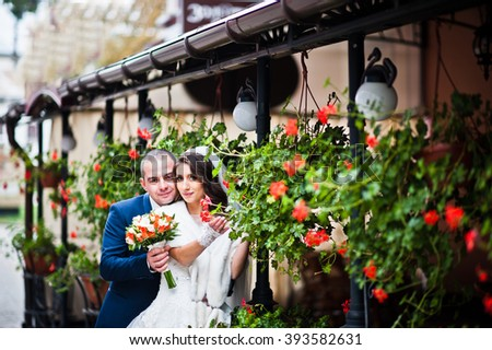 Wedding couple near cafe with flowers on the terrace