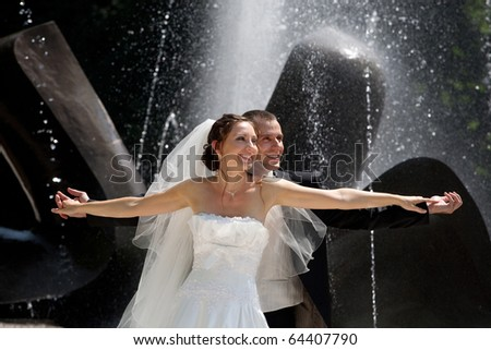 wedding couple near the fountain - stock photo