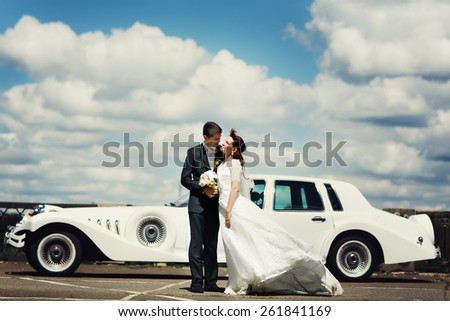 wedding couple near white car, cloudy sky background