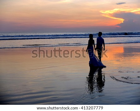 Wedding couple on the beach at sunset, Indonesia.