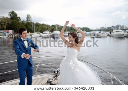 Wedding couple on the nature is dancing. Beautiful model girl in white dress. Handsome man in suit. Beauty bride with groom. Female and male portrait. Woman with lace veil. Lady and guy outdoors - stock photo