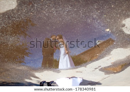wedding couple reflects in a puddle  - stock photo