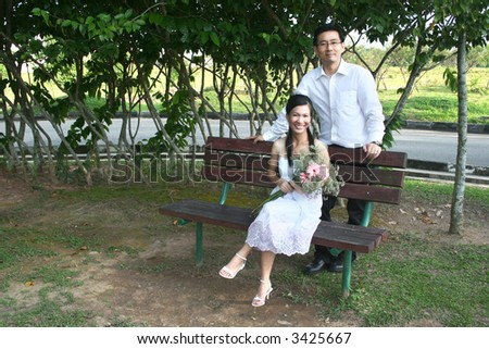 Wedding couple sitting on the bench in the park
