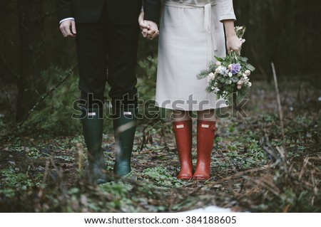 Wedding couple standing in the forest wearing colorful rubber boots - stock photo