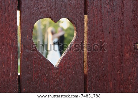 wedding couple viewed through heart-shaped hole in wood fence - stock photo