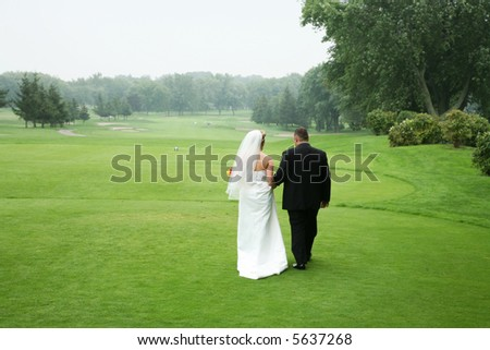 wedding couple walking at a golf course - stock photo
