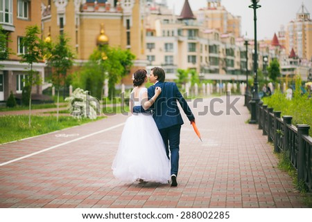 Wedding couple walking cheerfully in urban landscape. Bride and groom embracing and kissing. People in love. City streets. Wedding day. Horizontal color photo. - stock photo