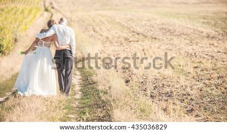 Wedding couple walking on the field - stock photo