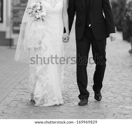 Wedding couple walking street, wedding fashion, black and white. - stock photo
