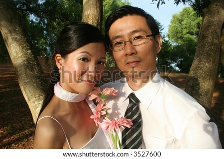 Wedding couple with pink daisy in the park - stock photo