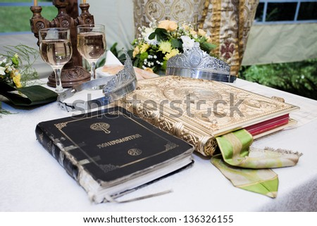 Wedding crowns, bible and wine glasses prepared for ceremony - stock photo