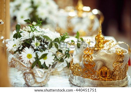 Wedding crowns stand behind a bouquet of chamomiles - stock photo