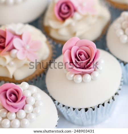 Wedding cupcakes in silver foil wrappers - stock photo