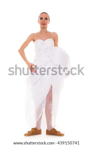 Wedding day. Running bride funny young woman wearing sport shoes isolated on white background