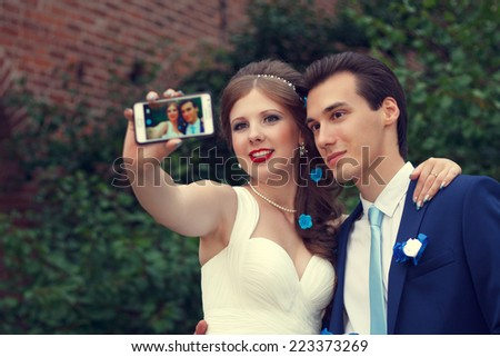Wedding day. The groom and the bride are photographed on phone