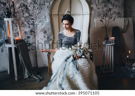 Wedding. Decor. Bride. The bride's bouquet. Artwork. Bride in blue and white dress sitting in a ? chair on a background of a gray textured wall and holding a bouquet of flowers and greenery