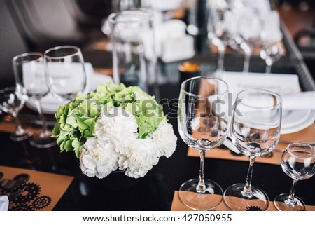 Wedding decor. Green and white hydrangea flowers in vase with cutlery and tableware on background. Reception.  - stock photo