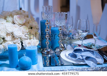 Wedding decor in blue. candles and flowers on the table - stock photo