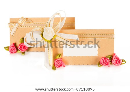 Wedding decor. Invitation card with pearl decoration and roses boutonniere on white background - stock photo