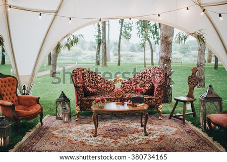Wedding. Decor. On the green lawn in the forest under a white tent lay carpet and standing vintage sofa and chairs, decorative items, flower arrangements, books and a set of croquet - stock photo