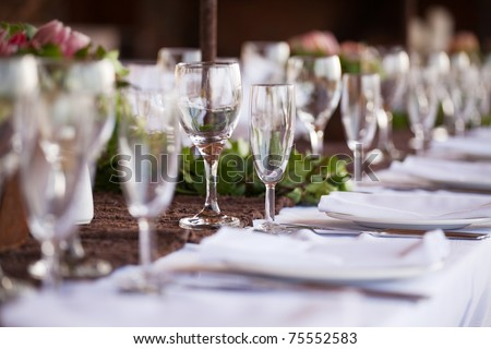 Wedding decor, wine glasses and champagne flutes on table. Selective focus - stock photo
