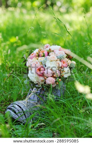 Wedding decoration details, closeup of flower bouquet in decorative wicker boot against green nature - stock photo