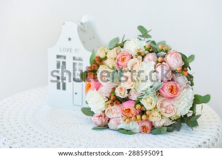 Wedding decoration details, closeup of flower bouquet with handmande house - stock photo