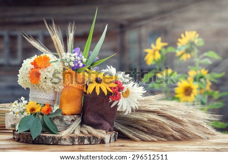 Wedding decoration in rustic style. Still life with summer flowers in a bags and ears of wheat. - stock photo