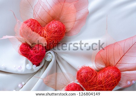 Wedding decoration made of white satin folded cloth and red hearts - stock photo