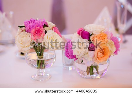 Wedding decoration on table. Floral arrangements and decoration. Arrangement of pink and white flowers in restaurant for luxury wedding event - stock photo