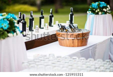 wedding decoration outdoors : Wine chilling and flower set on bar in Destination Wedding Celebration on the beach. romantic decorate set up on sea beach with flower and wine bottom in wedding party.