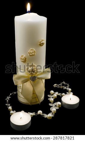 Wedding decoration: silver necklace with pearls and gold candles isolated on black