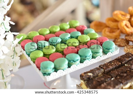 Wedding decoration with colorful cupcakes, cake and macarons. Wedding dessert table - stock photo