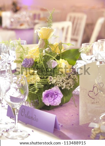 Wedding decoration with flowers and place card in yellow and violet - stock photo