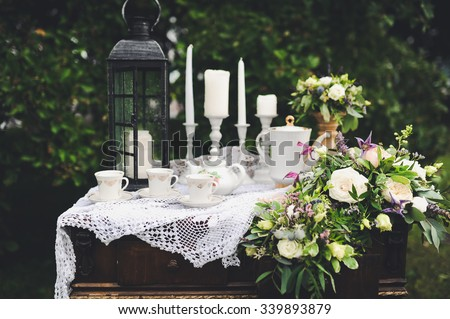 Wedding decorations for the ceremony in white flowers on green background, candles, tableware - stock photo