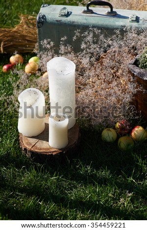 Wedding decorations with candles wild flowers apples and a suitcase. The scene is filled with backlighting