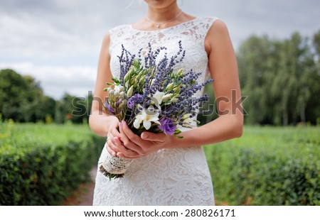 Wedding details. Close up of female hands holding bridal bouquet with lavender. - stock photo