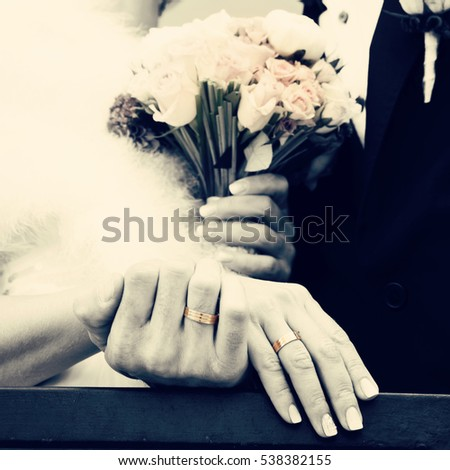 Wedding details, close up of hands with wedding rings and wedding bouquet, retro toned image