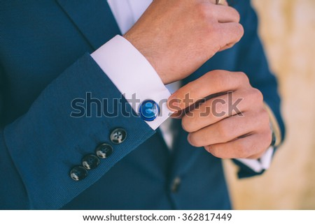 Wedding details, cufflinks, elegant male suit and hands  - stock photo