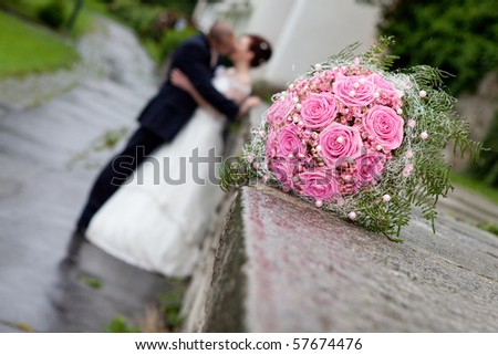wedding details - young marrieds behind a wedding bouquet - stock photo