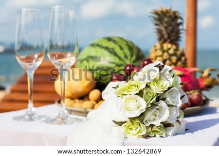 Wedding dinner on a sandy beach. Two loungers and a table with fruit.