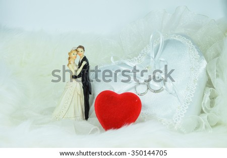 Wedding dolls, Wedding rings on white heart pillow, red heart on white background. concept of wedding. is symbols of love and couple - stock photo