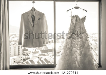 Wedding dress and suit hanging in a window. - stock photo