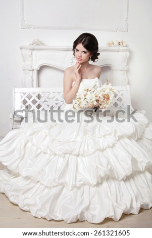 Wedding dress. Beautiful attractive bride model with voluminous skirt sitting on decorative garden bench against the modern wall. - stock photo