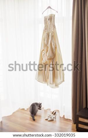 Wedding dress hanging by the window  - stock photo