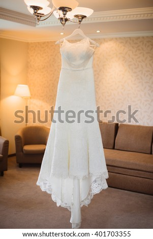 wedding dress hanging on luster at room