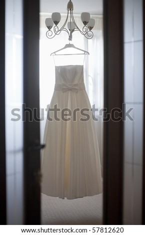 Wedding dress hanging on the chandelier in the room