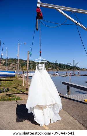 Wedding dress hung from a boat hoist at a yach club marina before the bride puts it on.