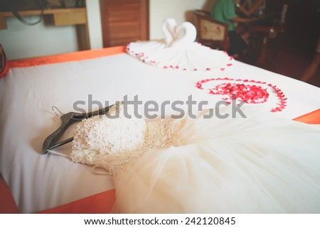 Wedding dress in room with rose petals, wedding decoration, Rose of Bouquet - stock photo